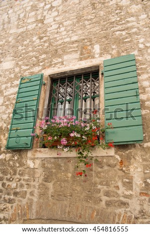 Green wooden windows with flowers in a stone house in Croatia