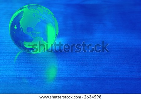Green world reflected on blue surface - add your text - stock photo