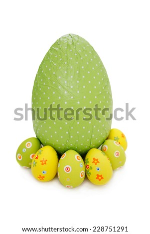 Green wrapped chocolate Easter Eggs and little ones on white background - stock photo