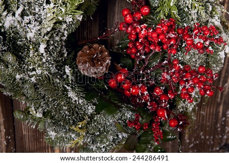 green wreath with red berries on wooden door - stock photo