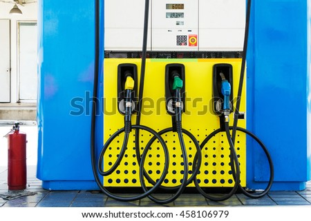 Green,Yellow and Blue fuel nozzles in the fuel dispenser in the Petrol Station