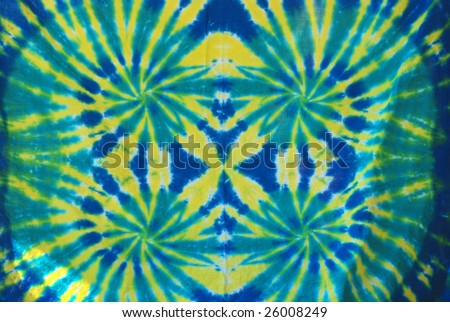 Green, yellow and blue tie dye design on fabric. - stock photo