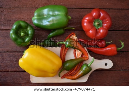 Green, yellow and red bell peppers and brown table
