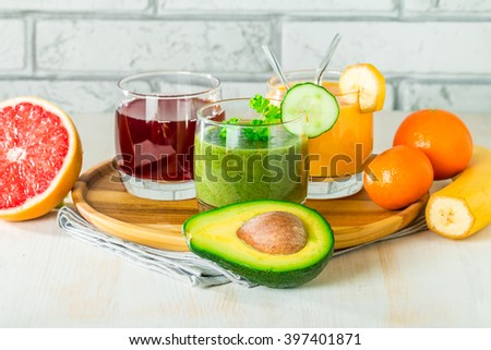 Green, yellow and red smoothies, juices, beverages, drinks variety with fresh fruits and vegetables on a white wooden background. - stock photo