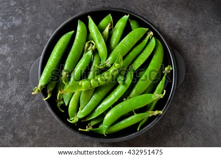 Green, young peas in a cast-iron plate on a black background
