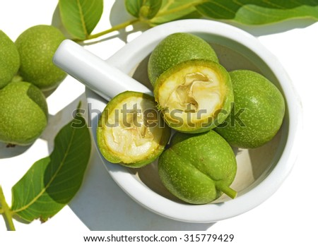 Green young walnuts in husks in pounder - stock photo