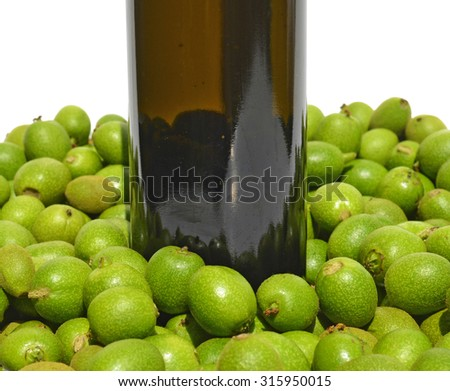 Green young walnuts in syrup bottle - stock photo