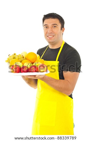 Greengrocer with yellow apron holding fruits on plateau isolated on white background - stock photo