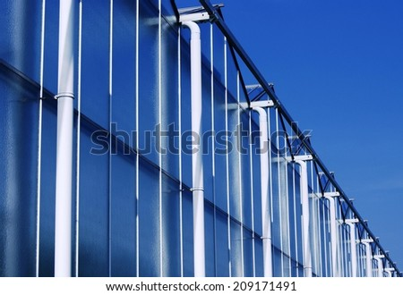 Greenhouse exterior with rainpipes and reflection of the blue sky in windows. The Netherlands, Europe - stock photo