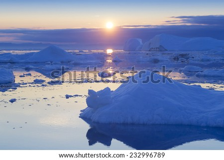 Greenland. Centuries-old thicknesses of glaciers. Icebergs of unusual forms. Research of a phenomenon of global warming and catastrophic thawing of ices. - stock photo