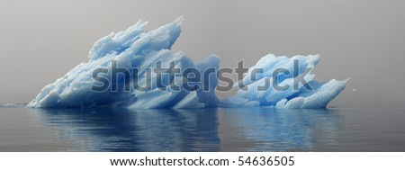 Greenland. Unusual blue ice among a dense fog on a still water. - stock photo