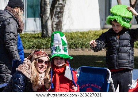 """Greenwich, CT, USA - March 22nd, 2015: Spectators enjoying the  """"Annual St. Patrick's Day"""" parade held on March 22nd, 2015 in downtown Greenwich Connecticut.  - stock photo"""