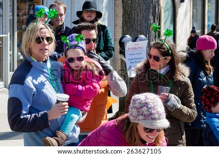 "Greenwich, CT, USA - March 22nd, 2015: Spectators enjoying the  ""Annual St. Patrick's Day"" parade held on March 22nd, 2015 in downtown Greenwich Connecticut."