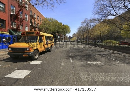 Greenwich village, New York City - April 21, 2016 : A yellow school bus in Greenwich Village parked in front of old resident  - stock photo