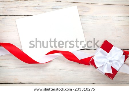 Greeting card and gift box with ribbon over white wooden table background - stock photo