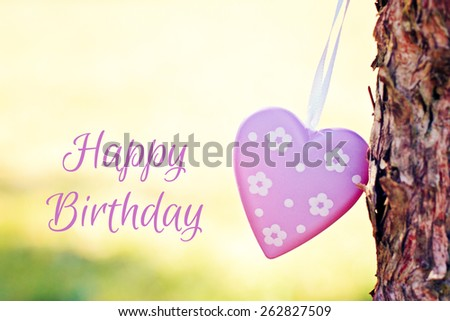 greeting card - heart against meadow - happy birthday - stock photo