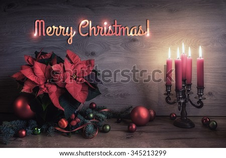 """Greeting card """"Merry Christmas!"""" with candles and decorated Christmas tree on wooden table. This image is toned. - stock photo"""