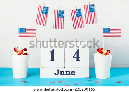 """Greeting card on the day of the American flag, two desserts with cream, strawberries and American flags, perpetual calendar with the words """"June 14"""",  American flags hanging on a rope with clothespins - stock photo"""