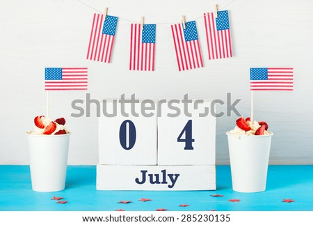 """greeting card on the Independence Day of America, two desserts with cream, strawberries and American flags, perpetual calendar with the words """"Jule 4, American flags hanging on rope with clothespins  - stock photo"""