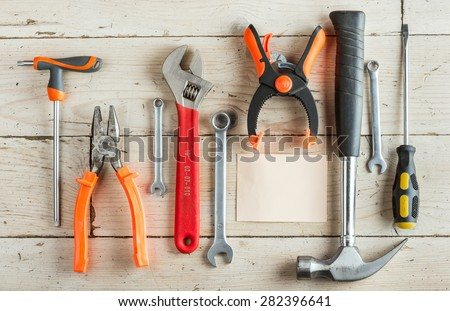 Greeting Card to Happy Father's Day, concept, set of different tools: a hammer, pliers, wrench, screwdriver, various spanners, clamp on a wooden background and tablet for  inscription, text, top view - stock photo