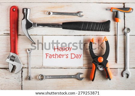 "Greeting Card to Happy Father's Day, concept, set of different tools: a hammer, wrench, screwdriver, various spanners, clamp on a wooden background and tablet with text ""Happy Father's Day""  top view - stock photo"