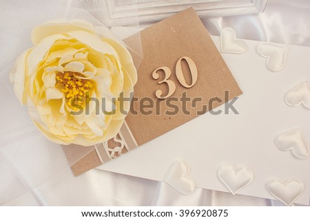 Greeting card with birthday. Invitation to the wedding anniversary. Envelope, hearts and flowers on the satin background. Anniversary thirty years. - stock photo