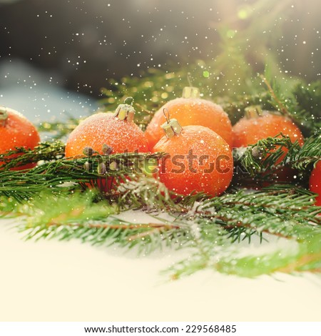 Greeting Card with Tangerines as Fir-tree Toy and Branch of Coniferous on Snow, with boke and snowflakes, toned square image - stock photo