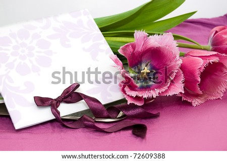 Greeting card with violet tulips and ribbon - stock photo