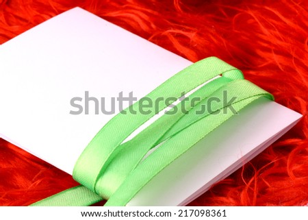 Greeting card with white paper and green bow - stock photo
