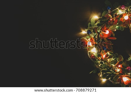 Greeting Season concept.Christmas wreath with decorative light on dark wood background