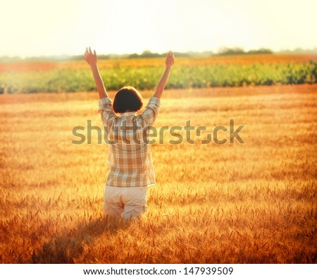 Greeting to the Sun - Women in a wheat field at sunset - stock photo
