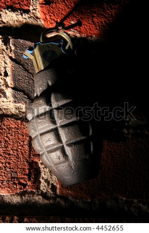Grenade hanging on nail in brick wall (side lighting) - stock photo