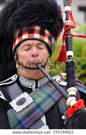 GRETNA GREEN - JUNE 12: Piper in traditional Scottish outfit plays on bagpipes in Gretna Green, United Kingdom on June 12, 2013. - stock photo