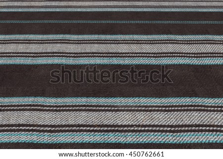 Grey and black striped woolen blanket texture. Nature and summer holidays background. Outdoor family travel and vacation wallpaper with plaid rug pattern. Blue and white lines fabric cloth.  - stock photo