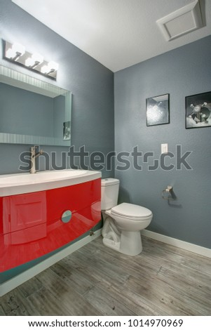 Grey and red bathroom design in a freshly renovated home. Gray walls complementing a modern red vanity cabinet accented with oval sink.