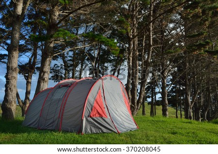 Grey and red tent camping outdoors in the nature - stock photo