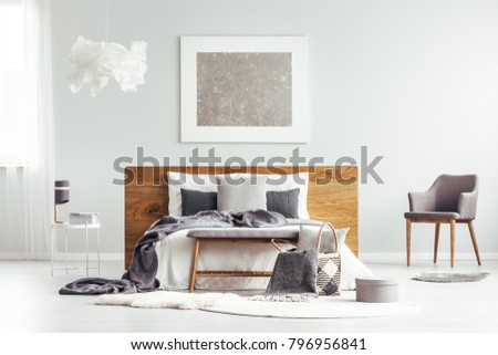 Grey Armchair And Rugs Next To Bed In Modern Bedroom Interior With Box And  Silver Painting
