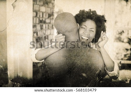 Grey background against happy couple embracing and cheering