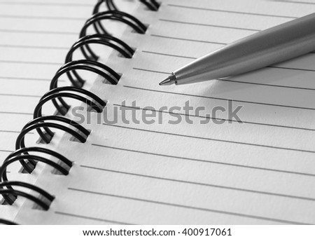 Grey ball pen on opened line notebook, selective focus (colored filter effect)