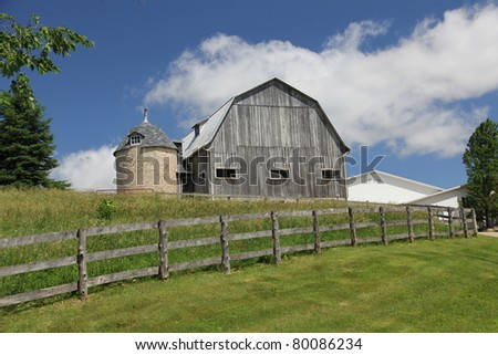 grey barn with board fence - stock photo