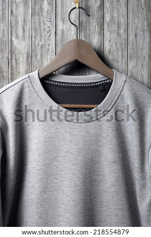 Grey blank jumper hanging on wood wall - stock photo