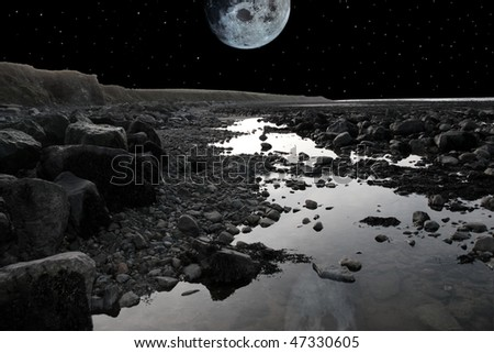 grey boulders and rocks on beale beach co kerry ireland on a cold winters night under a full moon - stock photo