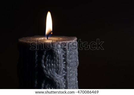 Grey candle on black background