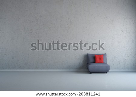 Grey chair with red cusion in front of concrete wall with copy space - stock photo