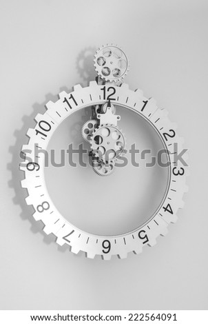 Grey clock with gears on grey background - stock photo