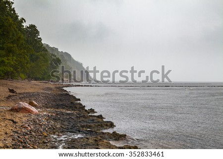 Grey clouds over Baltic sea sand coast - stock photo