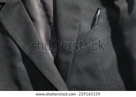 Grey color suit represent the formal uniform for businessman in the scene appear chrome ball pen also