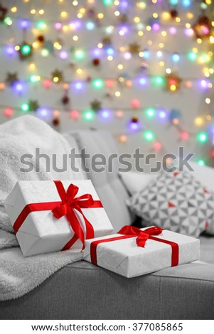 Grey couch with gifts on Christmas lights background
