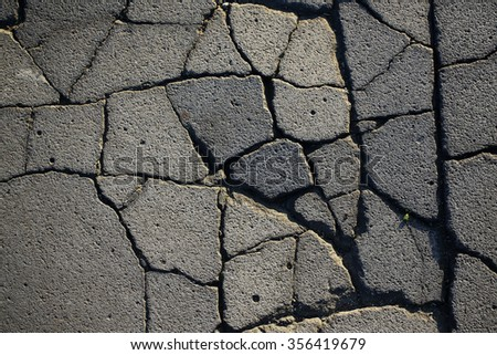 Grey cracked destroyed asphalt ground grunge style backdrop natural background zone of destroying urban road texture surface closeup, horizontal picture  - stock photo