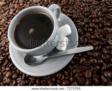 Grey cup of coffee with beans - stock photo